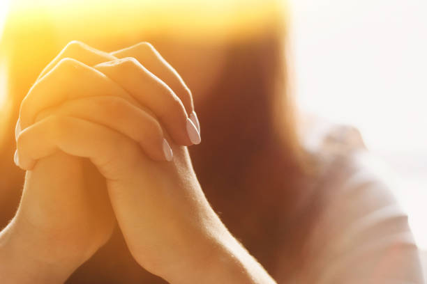 милая красивая девушка сложила руки в молитве. женщина просит бога о помощи - white background стоковые фото и изображения