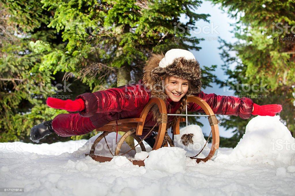 Cute beautiful girl having fun on snow sledge stock photo