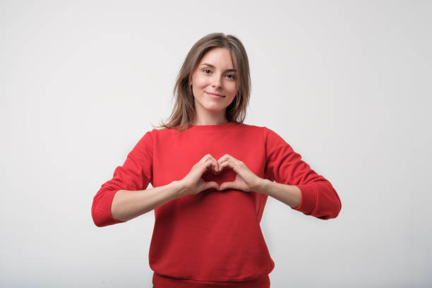 Cute beautiful girl in love making heart with fingers and smiling stock photo