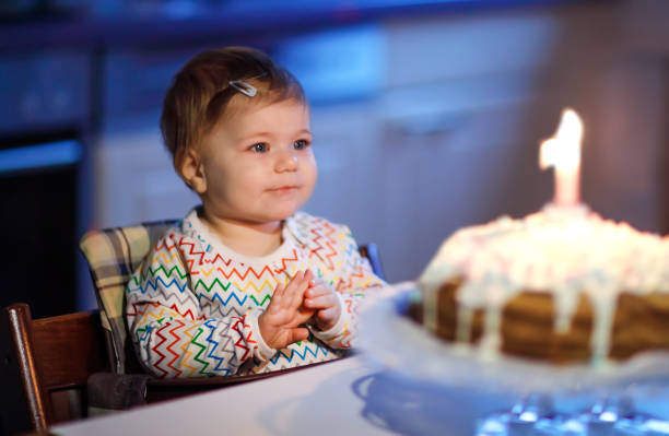 Cute beautiful little baby girl celebrating first birthday. Child blowing one candle on homemade baked cake, indoor. Birthday family party for lovely toddler child, beautiful daughter Cute beautiful little baby girl celebrating first birthday. Child blowing one candle on homemade baked cake, indoor. Birthday family party for lovely toddler child, beautiful daughter. birthday wishes for daughter stock pictures, royalty-free photos & images