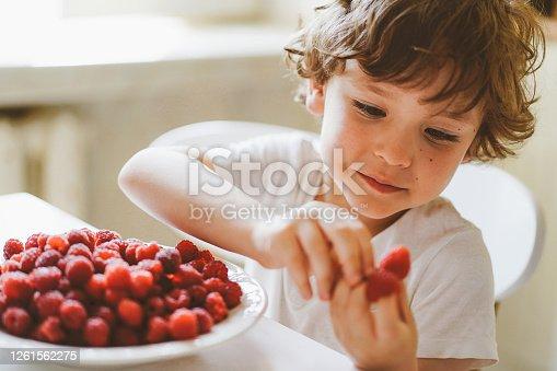Cute beautiful little boy eating fresh raspberries. Healthy food, childhood and development. Happy kid at home.