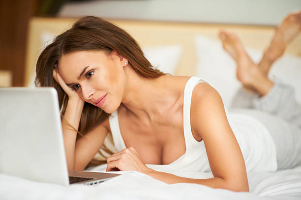 Cute beautiful woman lying on bed in bedroom with laptop stock photo