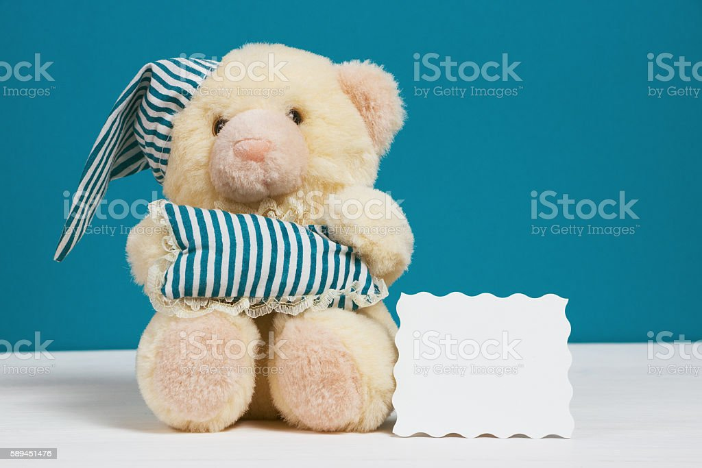 Cute beige bear with a nightcap, pillow and card on - Photo