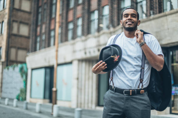 Cute black gentleman in city One man, Handsome young gentleman standing on the street downtown in city. suspenders stock pictures, royalty-free photos & images
