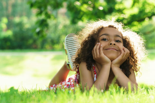 Cute black girl lying on a grass in a city park stock photo