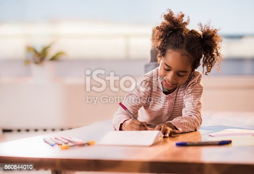 Happy African American girl relaxing on the table at home and coloring in notebook.