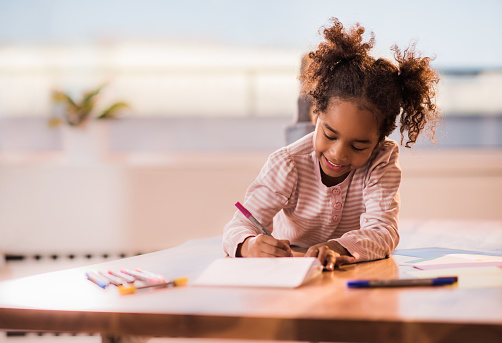 Cute Black Girl Relaxing At Home And Drawing On A Paper — стоковые фотографии и другие картинки Африканская этническая группа