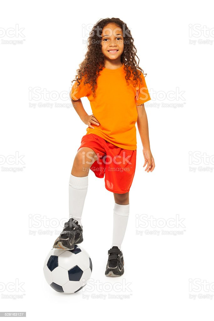 Cute black girl stand on soccer ball in studio stock photo