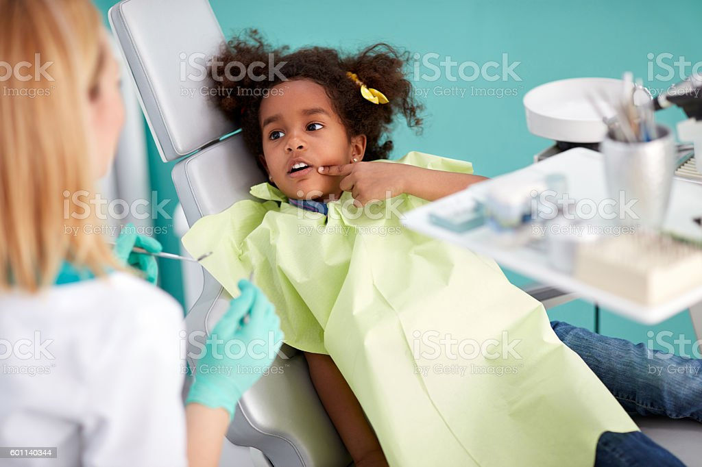 Cute black kid showing aching tooth stock photo