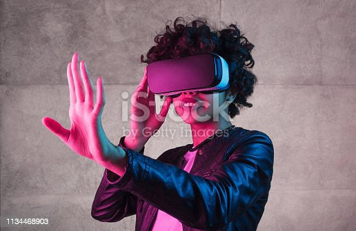 Lovely African American teen girl trying to interact with virtual reality while standing near concrete wall under bright light