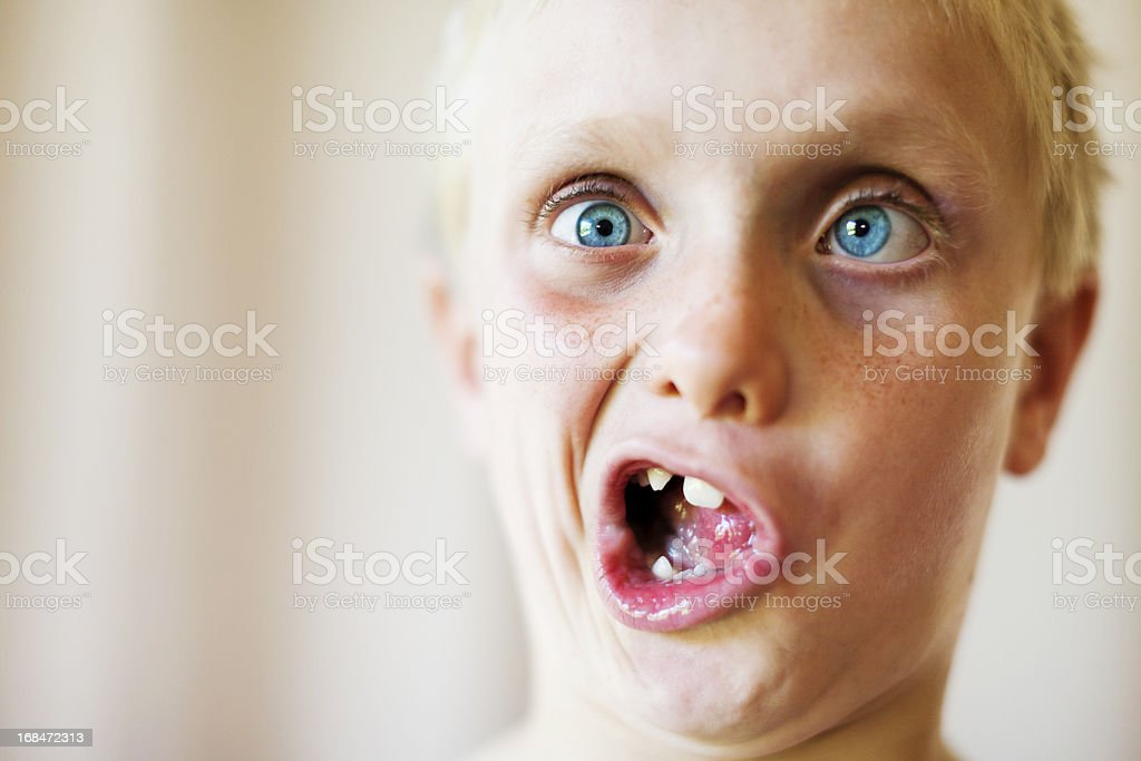 Cute blond 8 year old boy makes zany face stock photo