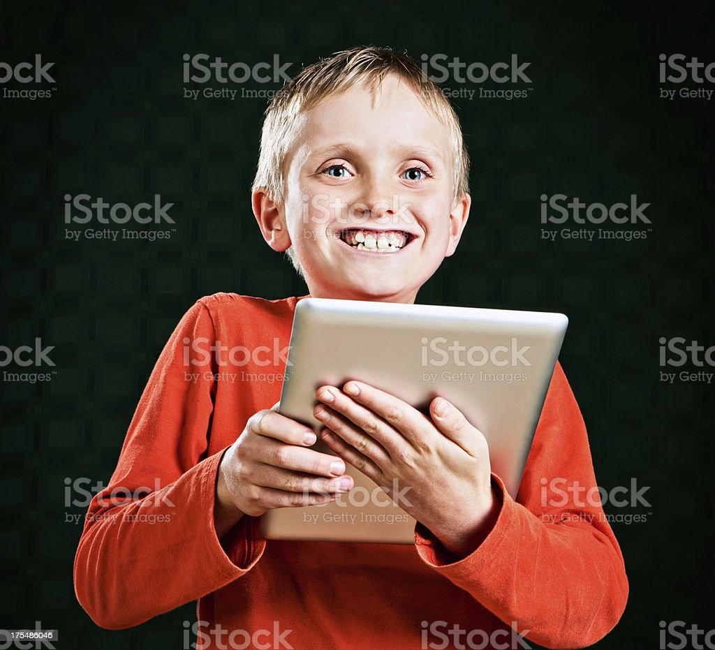 Cute blond boy holds tablet pc smiling delightedly royalty-free stock photo