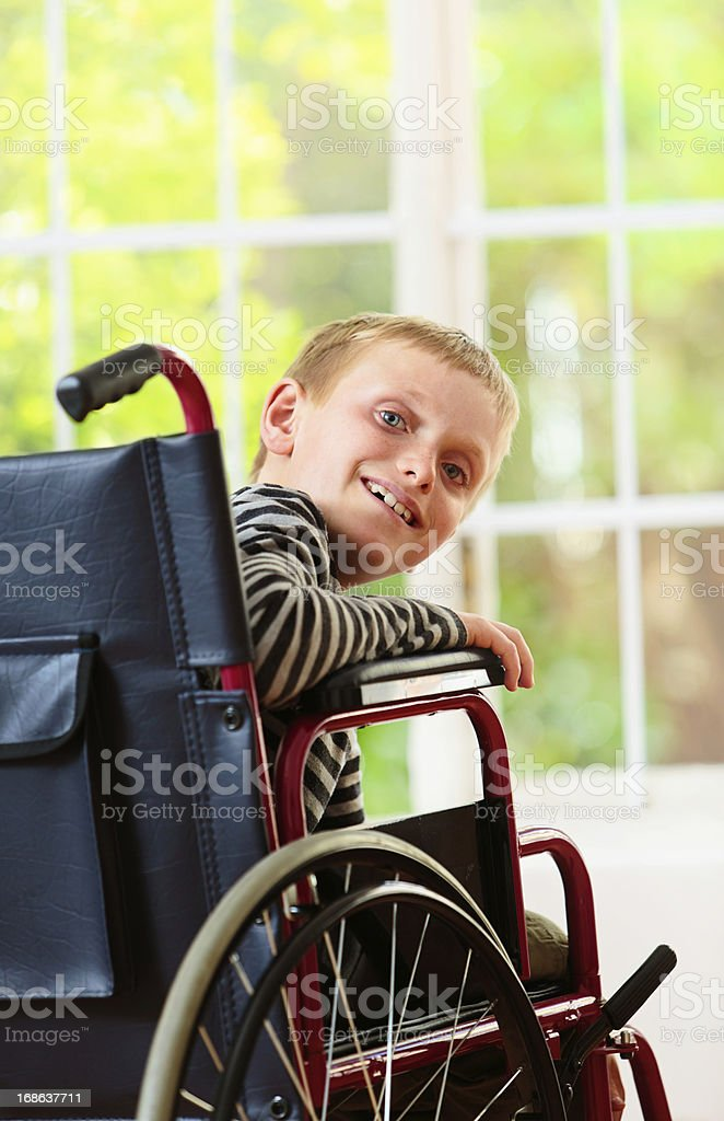 Cute blond boy in wheelchair smiles cheerfully over his shoulder stock photo