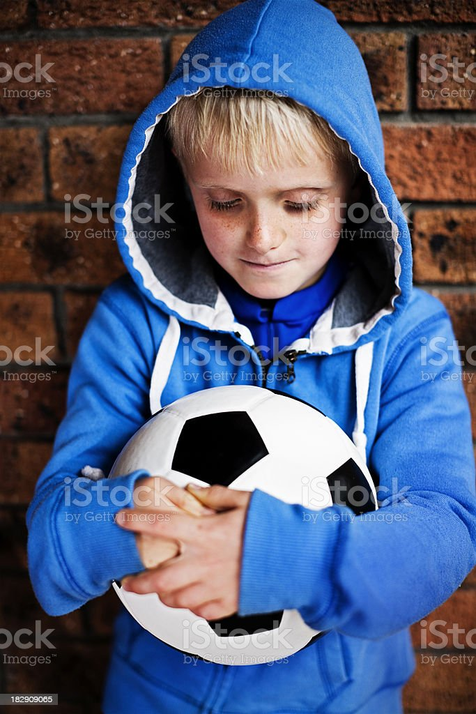 Cute blond boy looks down at  soccer ball he's holding royalty-free stock photo