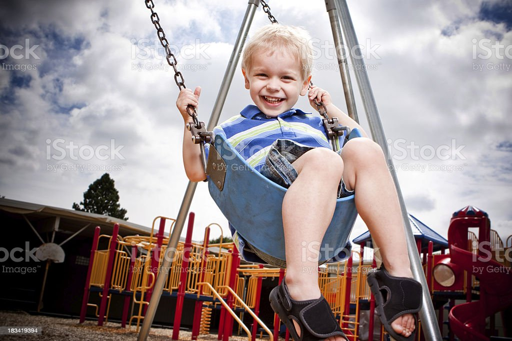 Cute Blond Boy Swinging at the Playground royalty-free stock photo