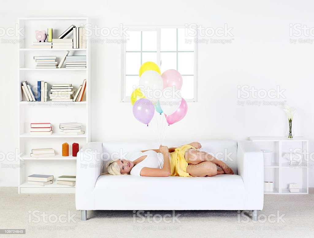 Cute blond female laying on sofa holding balloons royalty-free stock photo