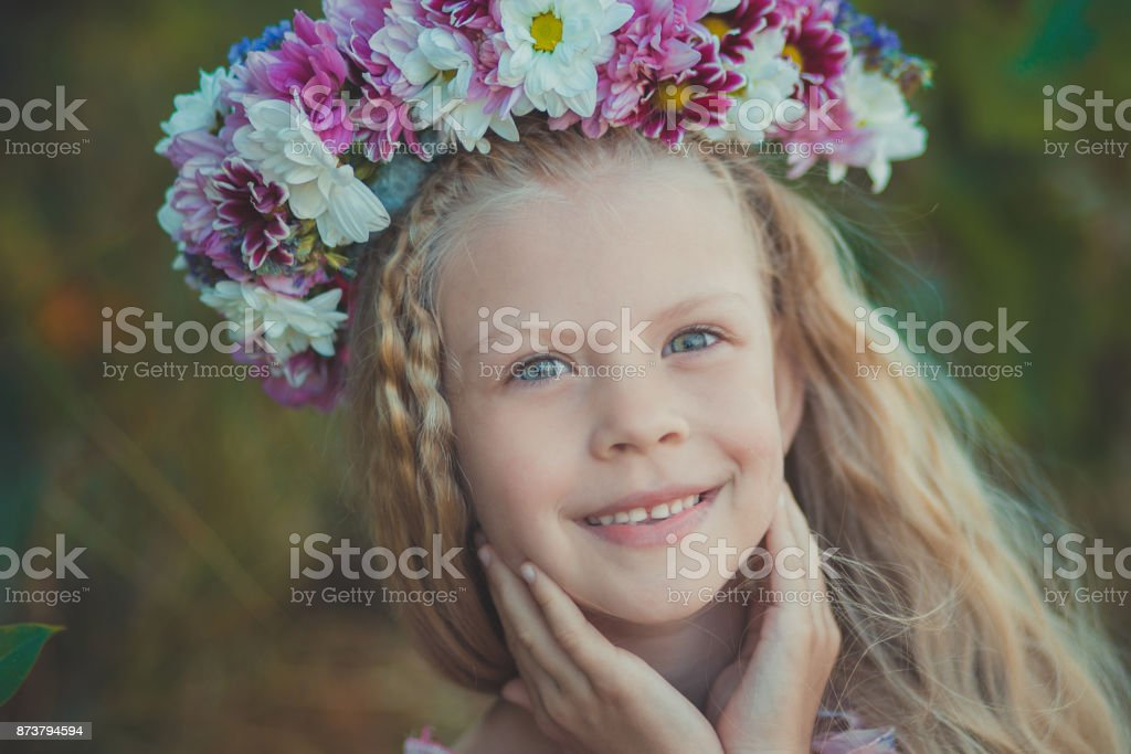 Cute blond girl with blue eyes close portrait wearing wild flowers wreath on top head smiling and looking to camera with eyes full of love joy and life. stock photo