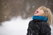 Cute blond kid boy catching snowflakes with his tongue while walking in a winter park. Child having fun with snow outdoors.