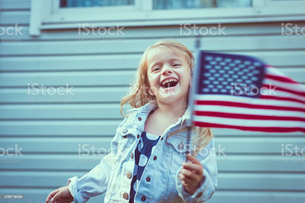 Cute blond little girl laughing and waving american flag stock photo