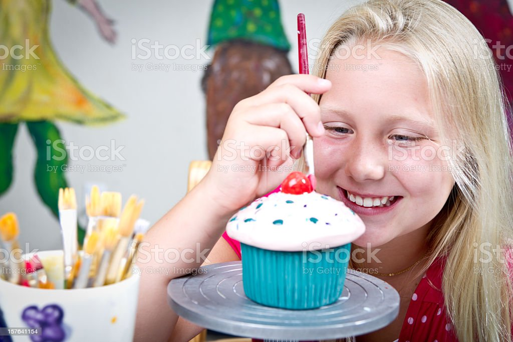Cute Blond Ten Year Old Girl Painting Pottery stock photo