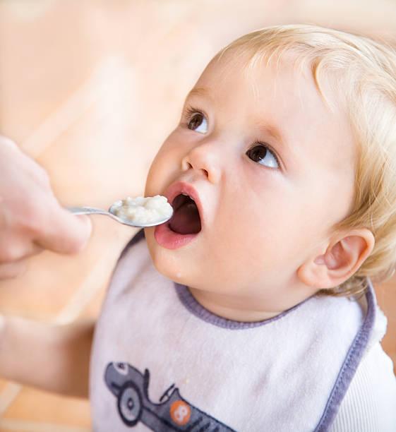 Süßes Blondes Kleinkind – Junge isst Haferbrei von spoon – Foto