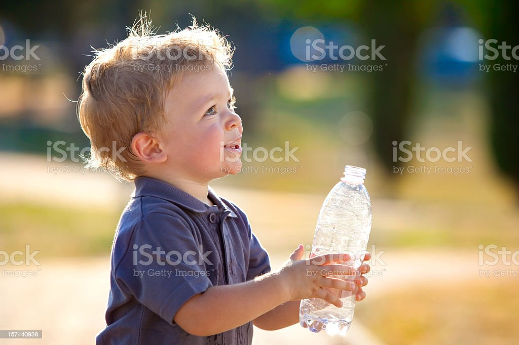 Cute blond toddler in the outdoors holding a water bottle royalty-free stock photo