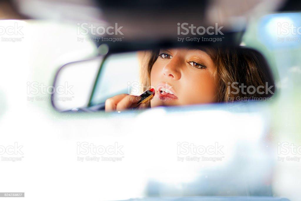 Linda loira mulher aplicando batom em um carro - foto de acervo