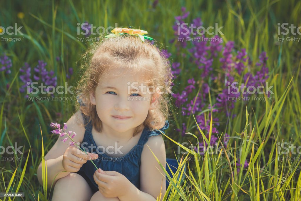 Cute blond young girl child stylish dressed in blue jeans dress posing on meadow of forest wild mayweed.Adoreable scene stock photo
