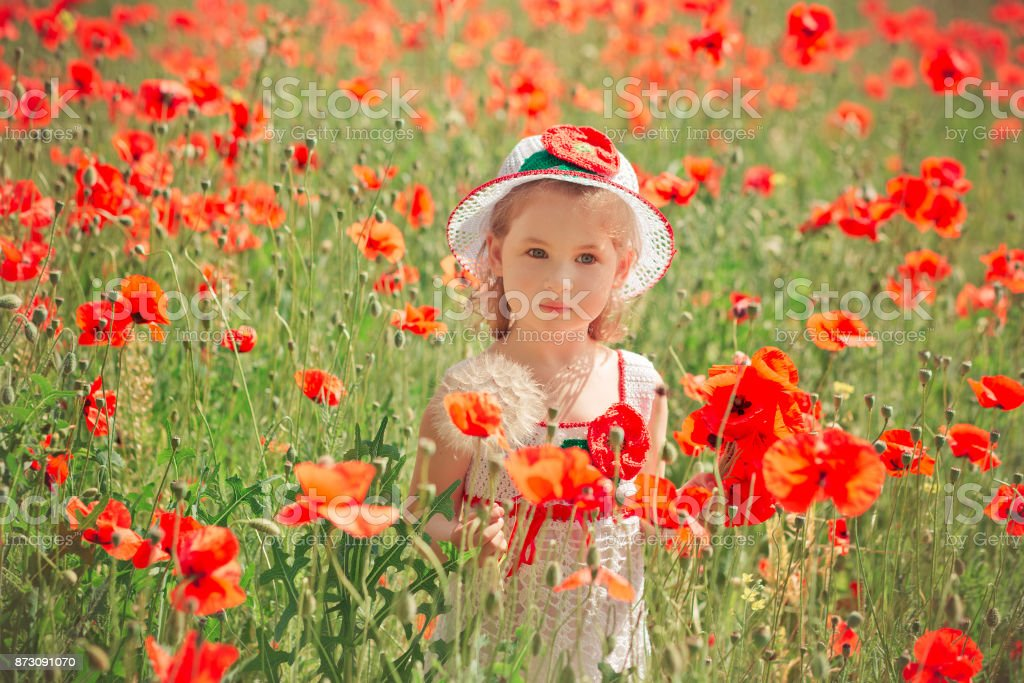 Cute blond young girl child stylish dressed in white handmade hooked dress wearing airy hat top posing on meadow of forest poppy poppies Adoreable scene stock photo