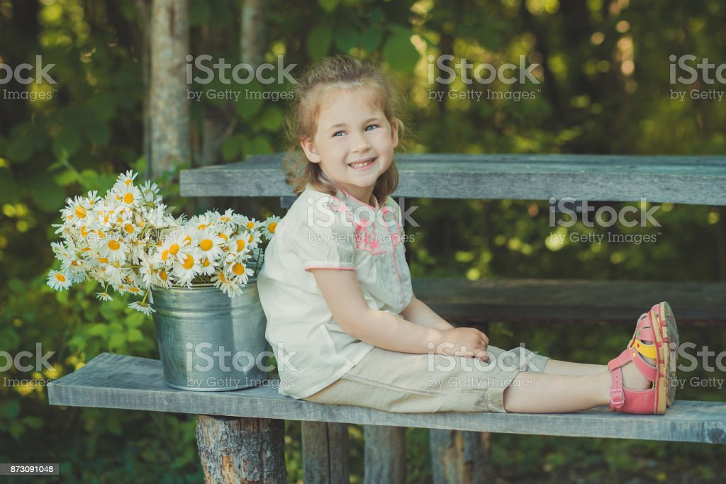 Cute blond young girl child stylish dressed in white shirt and short pants sitting on wooden bench posing bucket full of daisy chamomile mayweed.Adoreable scene stock photo