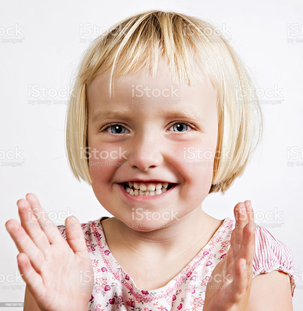 Cute blonde 3 year old smiles and claps hands stock photo