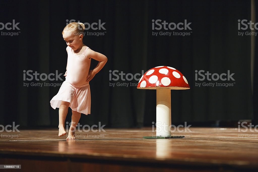 Cute blonde 4 year old ballerina dances round a mushroom stock photo