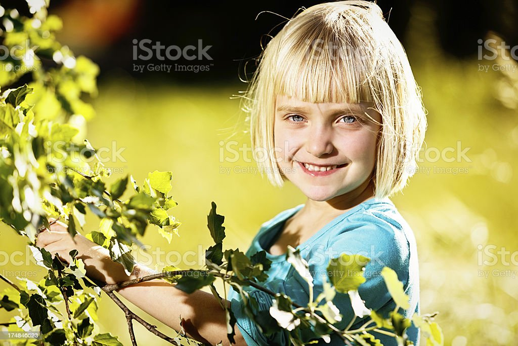 Cute blonde 5-year-old girl smiling by springtime tree stock photo