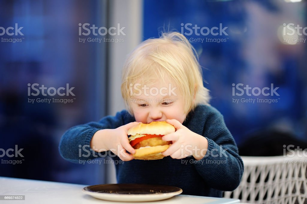 Cute blonde boy eat hamburger at fast food restaurant stock photo