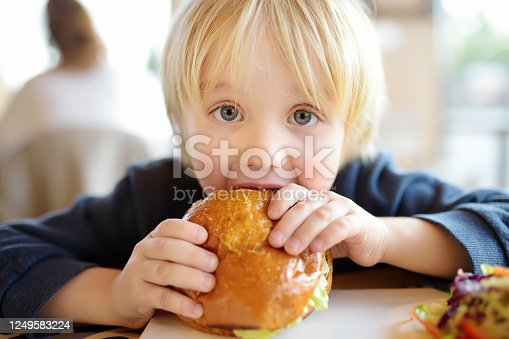 Cute blonde boy eating large hamburger at fast food restaurant. Unhealthy meal for kids. Junk food. Overweight problem child.