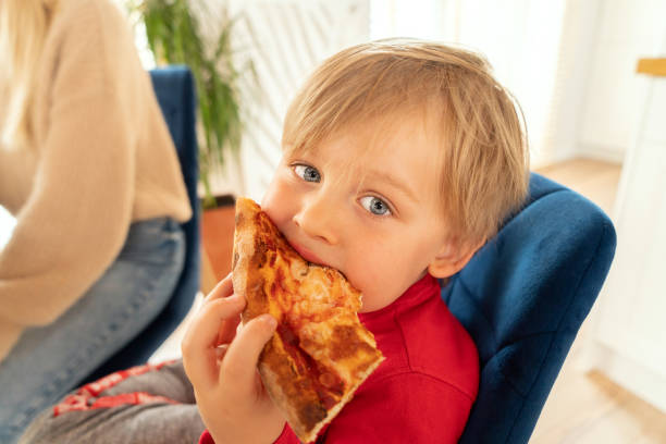 leuke blonde jongen die plak van pizza eet. - dikke pizza close up stockfoto's en -beelden