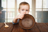 Cute blonde boy shows empty plate, hunger concept