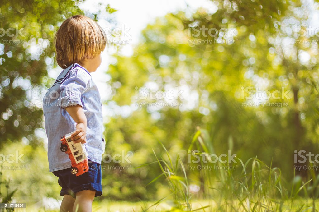 Cute blonde child holding a truck stock photo