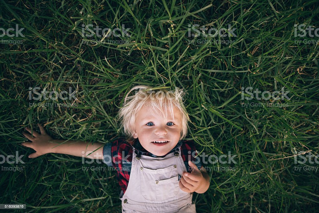 Cute blonde child lying on the grass stock photo