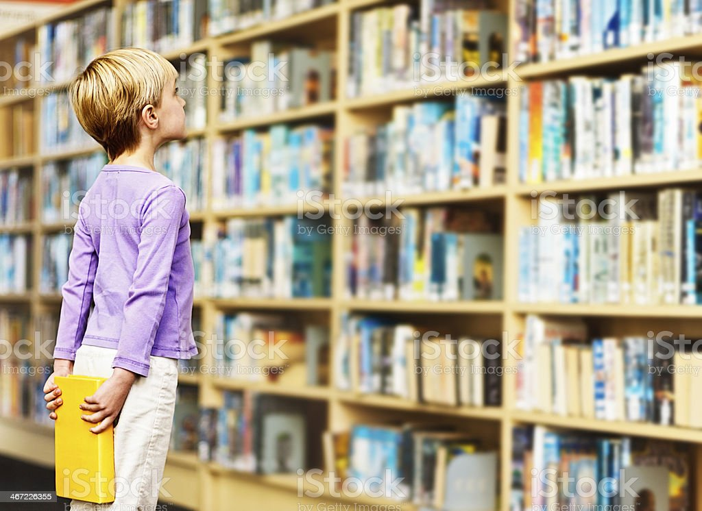 Cute blonde elementary-age girl eyes library shelves eagerly stock photo