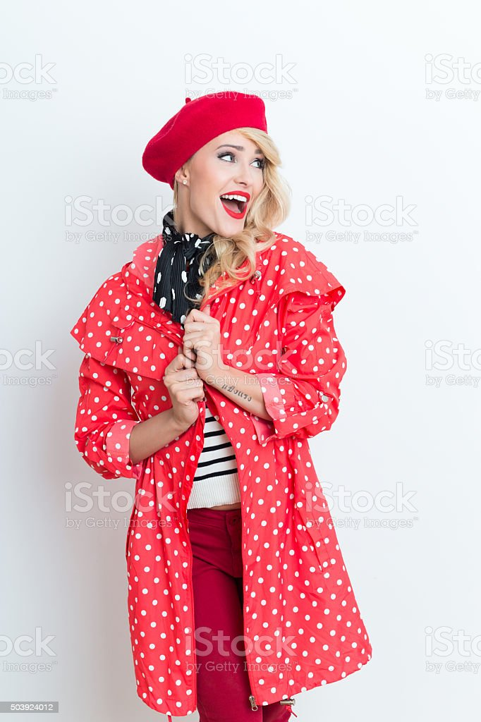 Cute blonde french woman wearing red beret and raincoat Portrait of beautiful blonde woman in french outfit, wearing a red beret and raincoat, looking away and laughing. Adult Stock Photo