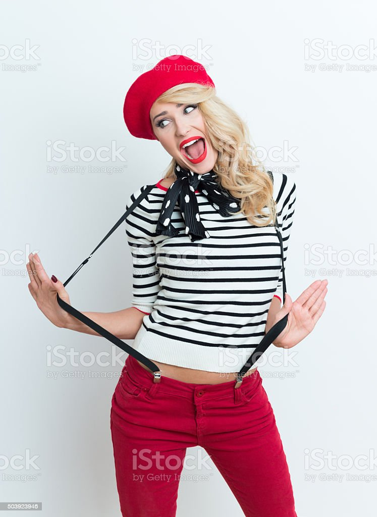 Cute blonde french woman wearing red beret Portrait of cute beautiful blonde woman in french outfit, wearing a red beret, striped blouse, suspenders and neckerchief. Adult Stock Photo