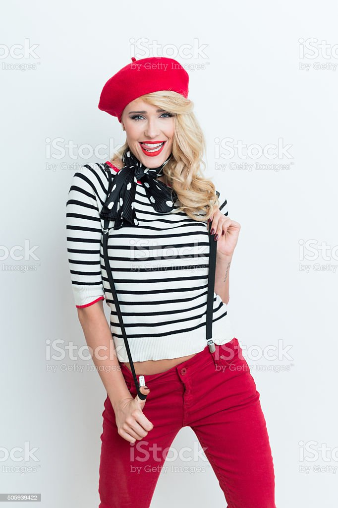 Cute blonde french woman wearing red beret Portrait of cute beautiful blonde woman in french outfit, wearing a red beret, striped blouse, suspenders and neckerchief, laughing at the camera. Adult Stock Photo