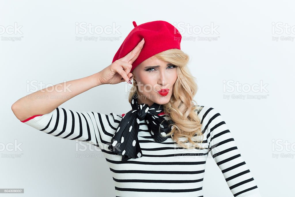 Cute blonde french woman wearing red beret, saluting Portrait of beautiful blonde woman in french outfit, wearing a red beret, striped blouse and neckerchief, sending kiss and saluting. Adult Stock Photo