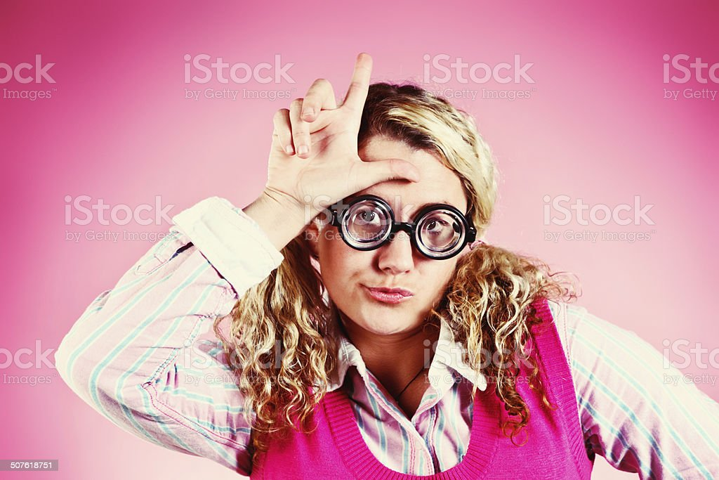 Cute blonde geek makes L for loser sign stock photo