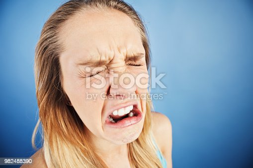 istock Cute blonde girl pulls a miserable face, crying and frowning 982488390
