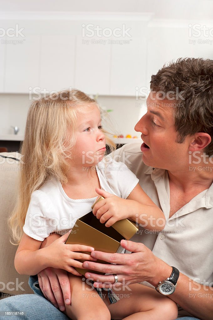 Cute blonde girl receives present from father stock photo