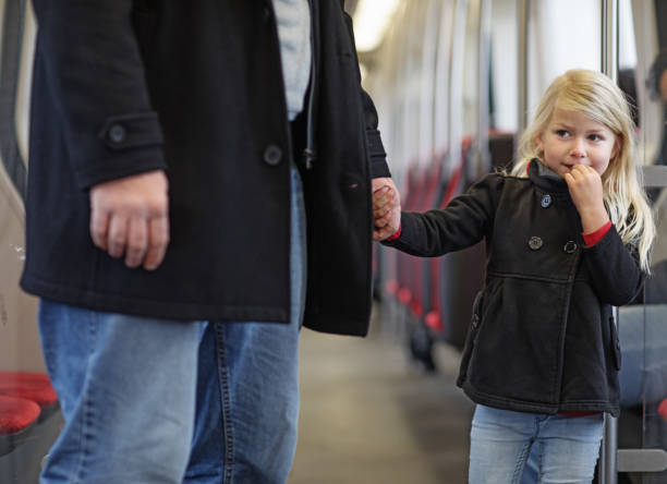 Cute blonde girl traveling on public transport with unknown male Cute blonde girl traveling on public transport with unknown male stranger stock pictures, royalty-free photos & images