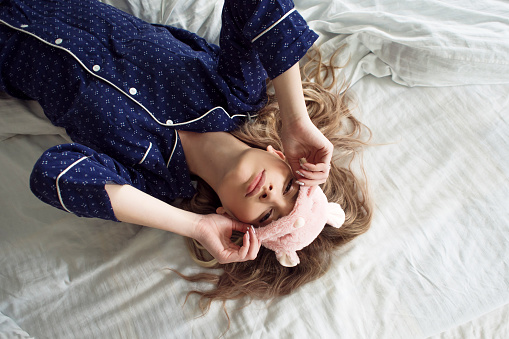 istock Cute blonde in her bed in blue pajamas and sleep mask, top view 855117644