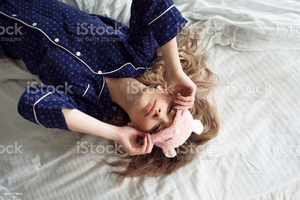 Linda rubia en su cama en pijama azul y antifaz para dormir, vista superior - foto de stock
